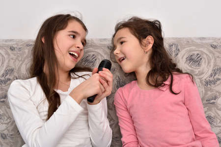 Two happy smiling sisters sitting on the sofa and singing a song on a microphone. Emotional portrait of happy children.