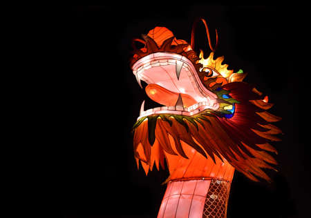 Chinese dragon lantern with bright glowing head isolated on the black background. Copy space on the left side. Zdjęcie Seryjne
