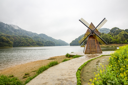 Landscape view of a windmill at the river side Stock Photo