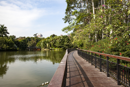 Landscape view of a walkway at the riverside in a park Stock Photo