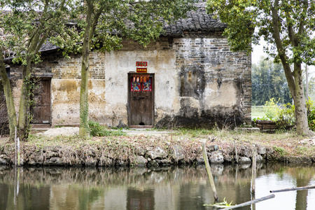 beside: ancient house beside pond . Editorial