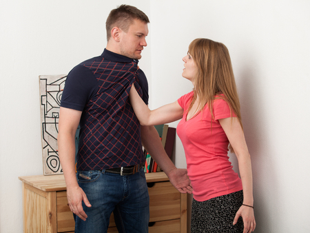 domestic abusive: the woman puts  hands over the mans chest and yells at him
