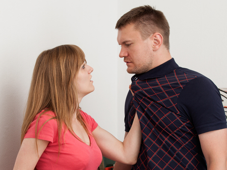 Womens aggression in the room. The woman grabbed her husband