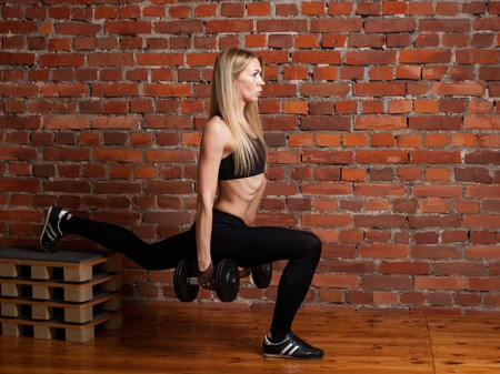 lunges: Athletic woman doing weighted lunges with dumbbells workout exercise for butt legs at the gym healthy lifestyle sport bodybuilding concept