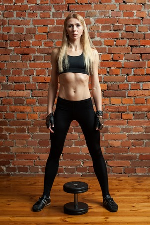 Young motivated woman training deadlift with dumbbell at the  gym Stock Photo