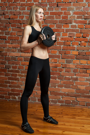 girl squatting: Young motivated woman is going to  train deadlift with a heavy disk  at the  gym