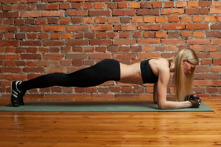 fitness, sport, training and lifestyle concept - woman doing plank exercises on mat at the  gym Stock Photo