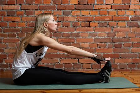 foreleg: Blond fitness model doing stretching exercise foreleg or feet muscles Stock Photo