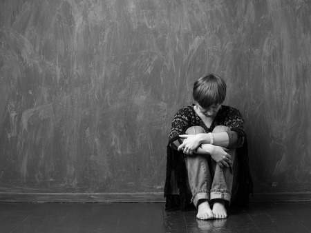 victim: Domestic violence -  hopeless victim is sitting on the floor hugging her knees. Black and white