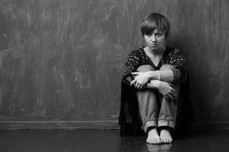 adult rape: Sad woman is sitting against the wall, reproachful look. Black and white