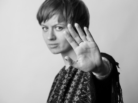 restraining: Young woman makes restraining gesture into the camera. Black and white image