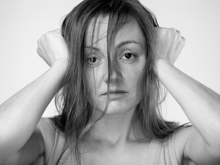 disheveled: Close up portrait of a sad woman in a beige shirt,  hands on the forehead , hair disheveled.  Black and white image on a white background.