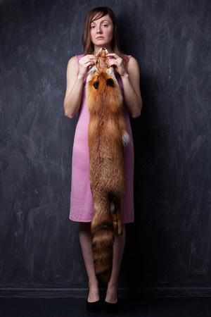 animal welfare: Sad woman and fox fur. Model holds the skin of the hands for animal welfare