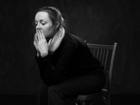 disoriented: Portrait of a young sad disoriented woman sitting on the chair, side view , grey background
