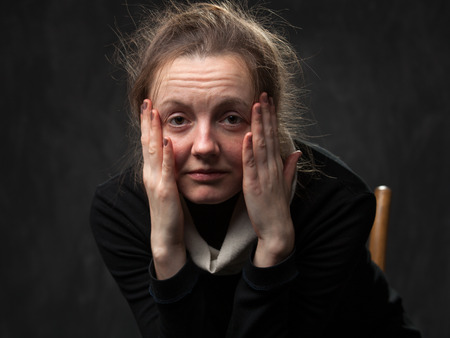 pale tired woman looking straight, touching her face with arms Standard-Bild