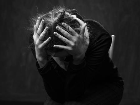 Retrato de una joven mujer triste, la cabeza se pone abajo, las manos están juntando la cabeza, fondo gris