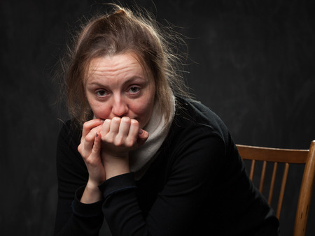 pale sad woman is sitting on the chair, half of her face is hidden by her fist (arms)