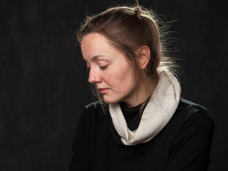 disoriented: Portrait of a young sad disoriented woman looking down, head is half-turned , grey background