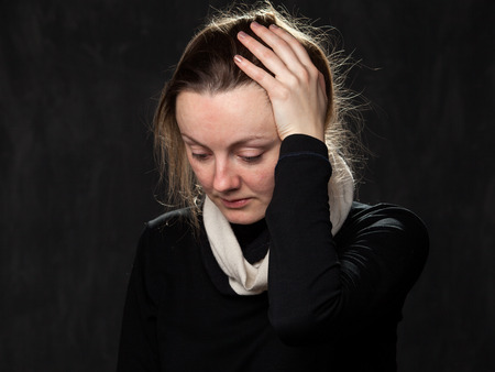 disoriented: Portrait of a young sad disoriented woman , grey background