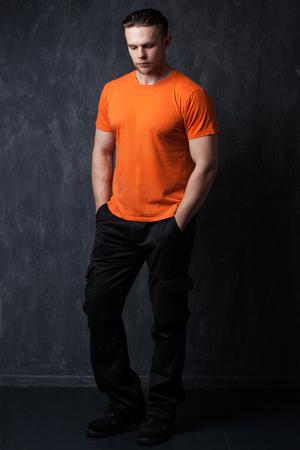 pantalones abajo: Hombre del atleta en una naranja camisa y pantalones negros, mirando hacia abajo, con las manos en los bolsillos, fondo gris
