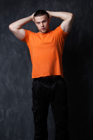 athletic wear: Portrait of a strong man in an orange shirt, hands behind head, grey background