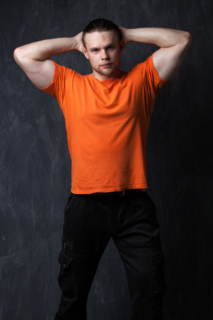 brawny: Brawny guy in the orange shirt holds his hands behind his head - the image on a gray background