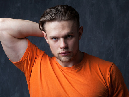 Portrait of a young muscular man in an orange shirt, a hand behind his head. Fitness model posing in a studio on a dark gray background. Stock Photo