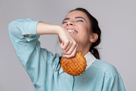 eyes opened: Young brunette woman with closed eyes, opened mouth and toothy smile going to throw away a cookie Stock Photo