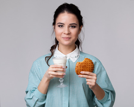 bisquit: Young brunette in a blue shirt with a glass of milk and a bisquit in the hands, isolated on white background