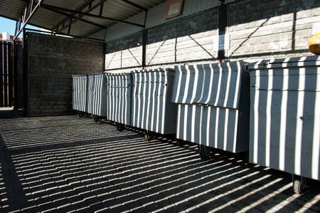 botes de basura: el juego de luces y sombras en la fila de botes de basura gris limpias
