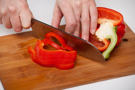 Cutting red pepper with a kitchen knife on a wooden board Reklamní fotografie
