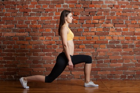 Young attractive sporty woman in the top and leggings makes attacks against the backdrop of a red brick wall.