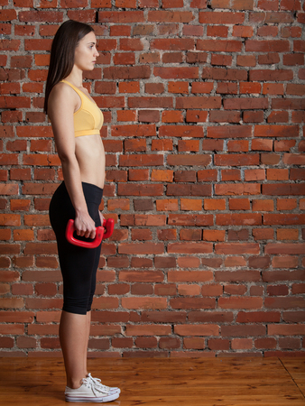 lunges: Young attractive sporty woman in the top and leggings going to do lunges with dumbbells on a background of red brick wall.