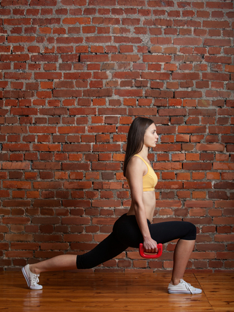lunges: Young attractive sporty woman in the top and leggings doing lunges with dumbbells on a background of red brick wall.