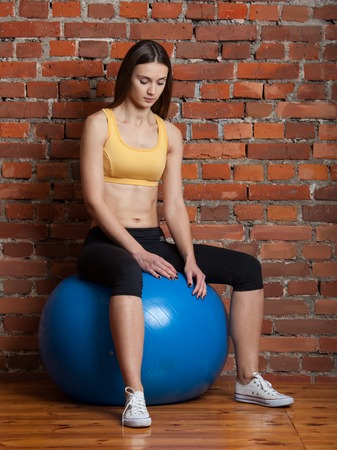 abdominal wall: Sport girl sitting on a big fitball, looking down
