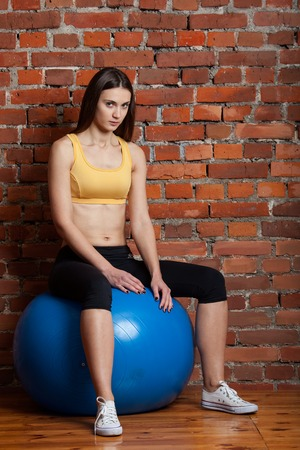 fitball: fitness brunette girl in yellow top sitting on fitball on brick wall background Stock Photo