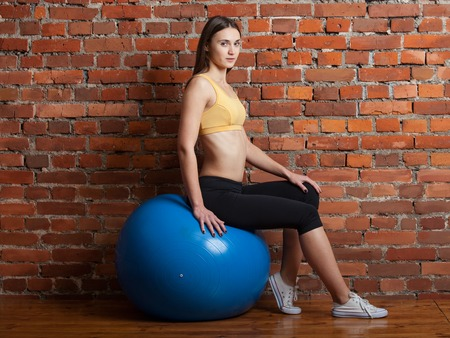 abdominal wall: Sport girl sitting on the big blue fitball looks in the picture