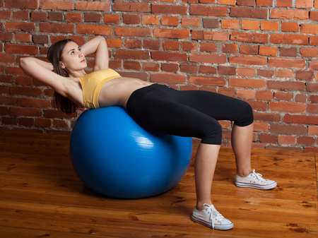 abdominal wall: Sports girl shakes her abdominal muscles on the big blue fit-ball Stock Photo