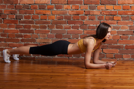 abdominal wall: Sport girl doing the bar and looks forward, on a red brick wall