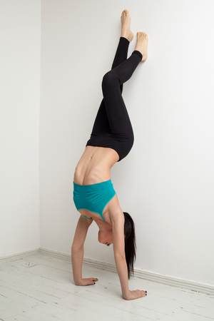 handstand: Sexy woman in a turquoise performs a handstand, near the wall