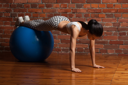 fitball: Fitness model pushed off the floor with his feet on a fitball, on a background of red brick wall.