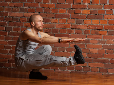 Athlete man performing squat on one leg (pistol squat exercise) at the gym , red brick wall background