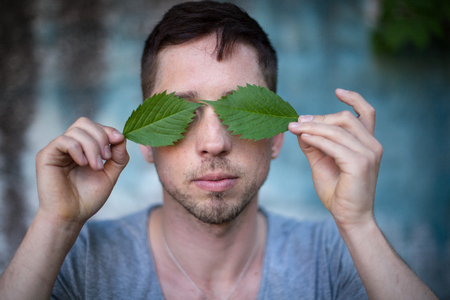 chestnut male: The young man closed both eyes chestnut leaves Stock Photo
