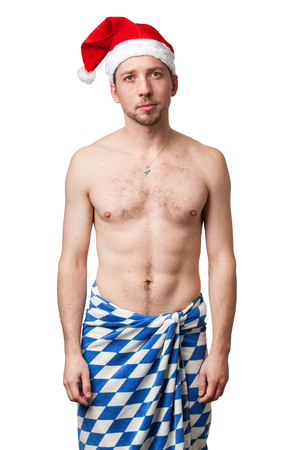 hat nude: Christmas portrait of a man in a red hat with a naked torso and blue checkered cloth on his hips, isolated on a white background Stock Photo