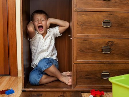 lonelyness: abuse and cruelty to children - little boy is hiding in a cupboard in the room, closing his ears by hands and crying Stock Photo
