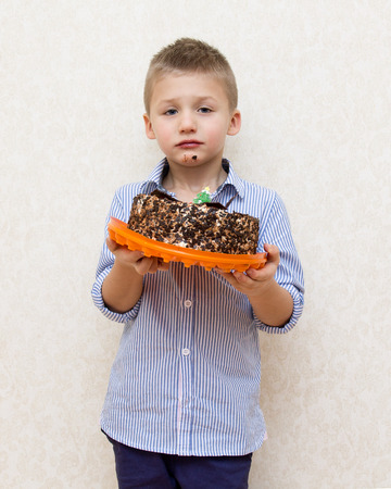 glutton: Little boy with a cake , his face is smeared with chocolate