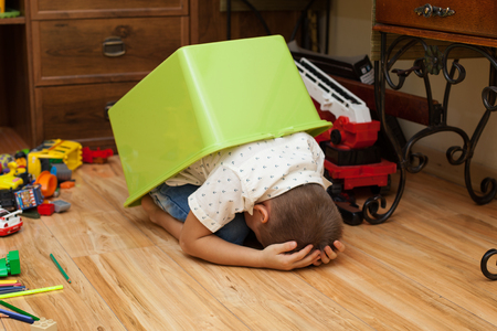 scared boy: abuse and cruelty to children - little boy is hiding in a box