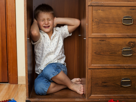 boy room: abuse and cruelty to children - little boy is hiding in a cupboard in the room, closing his ears by hands