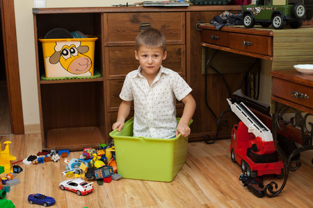 upbringing: upbringing and education- little boy ia sitting in the box on the floor in the room