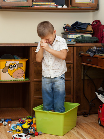 upbringing: upbringing and education- little boy ia standing in the box on the floor in the room Stock Photo